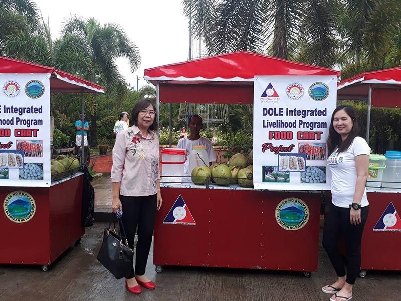 PAMPANGA. Department of Labor and Employment Pampanga Field Office head Arlene Tolentino (L) and Arayat PESO manager Arlyn Sebastian (R) lead the distribution of livelihood food carts to selected beneficiaries in Arayat town on July 29. (Contributed photo)