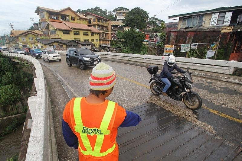 IMMINENT DANGER. Department of Public Works and Highways (DPWH) personnel monitor vehicles passing through Balili Bridge. A steel plate was placed July 31 to cover a hole near the end of the bridge. (Jean Nicole Cortes)