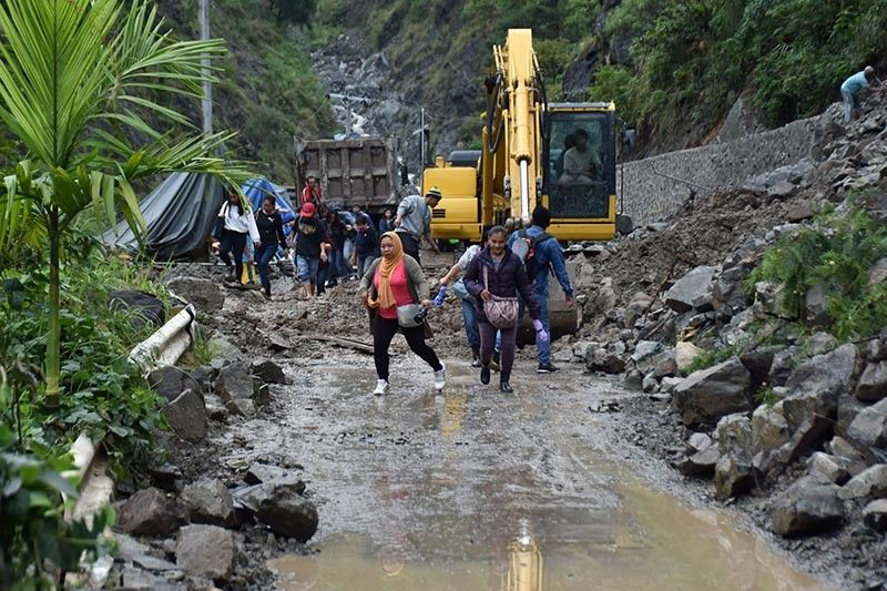 Despite the danger of the active landslide along a portion of Kennon Road at Barangay Camp 6, Sitio Camp 5, Tuba, Benguet, residents from the nearby barangays of Camp 4 to Camp 1 crosses the landslide affected area to transfer to vehicles waiting at the other side of the affected area en route to Baguio City. The Cordillera Regional DRRM Council has recommended the total closure of Kennon Road to residents and non-residents to prioritize safety particularly at the landslide affected area that started on July 27. (Redjie Melvic Cawis)