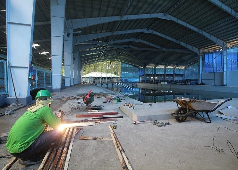 BAGUIO. Workers lay improvements for the P34 million worth upgrade for the Baguio athletic bowl swimming pool which is set to be finished this month. (Jean Nicole Cortes)