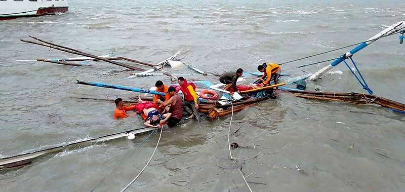 GUIMARAS. In this photo provided by the National Disaster Risk Reduction Management Council (NDRRMC), rescuers pluck ferry sinking victims from the choppy waters off Guimaras Sunday, Aug. 4, 2019 in Iloilo province in central Philippines. Philippine police say rescuers have plucked more bodies in rough seas where three ferry boats capsized after being buffeted by fierce wind and waves off two central provinces. (NDRRMC Via AP)