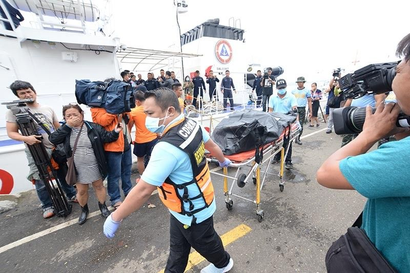 ILOILO. The body of one of those who died in the sinking of three motorized  bancas in Iloilo-Guimaras Strait is being carried out from the Philippine Coast Guard MRRV4411 BRP Cape Engaño. (Leo Solinap)
