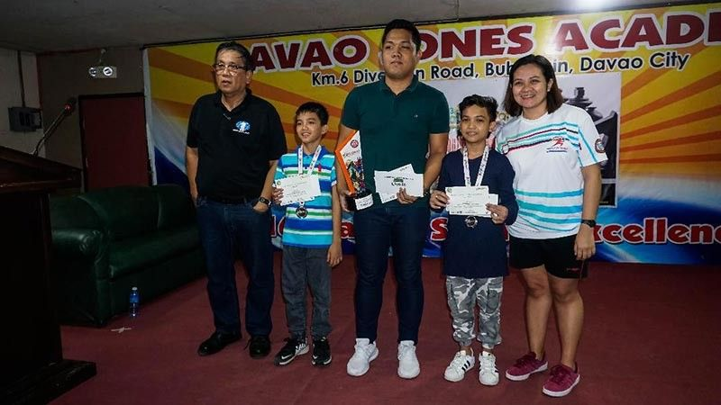 DAVAO. Bhing Joel Gimony, center, wins the championship trophy of the recently-concluded 34th Kadayawan Sports Festival Standard Chess Championship at the Davao Jones Academy Training Center in Buhangin, Davao City. Also in photo from left, tournament director Ronnie Tabudlong, third placer James Catayas, runner-up Wesley Jovan Magbanua and Irish Ortiz of Sports Development Division of the City Mayor's Office (SDD-CMO). (Photo by Leeroy A. Guzman/SDD-CMO)