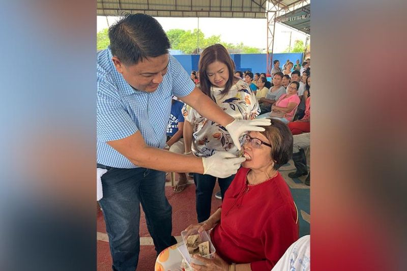 """PAMPANGA. Dr. Alfie Bonifacio fits a new set of dentures on an elderly patient in Lubao town. Looking on is Mayor Esmeralda Pineda, whose father, businessman Rodolfo """"Bong"""" Pineda, sponsored the free dentures and eyeglasses to 2nd District residents. (Contributed Photo)"""