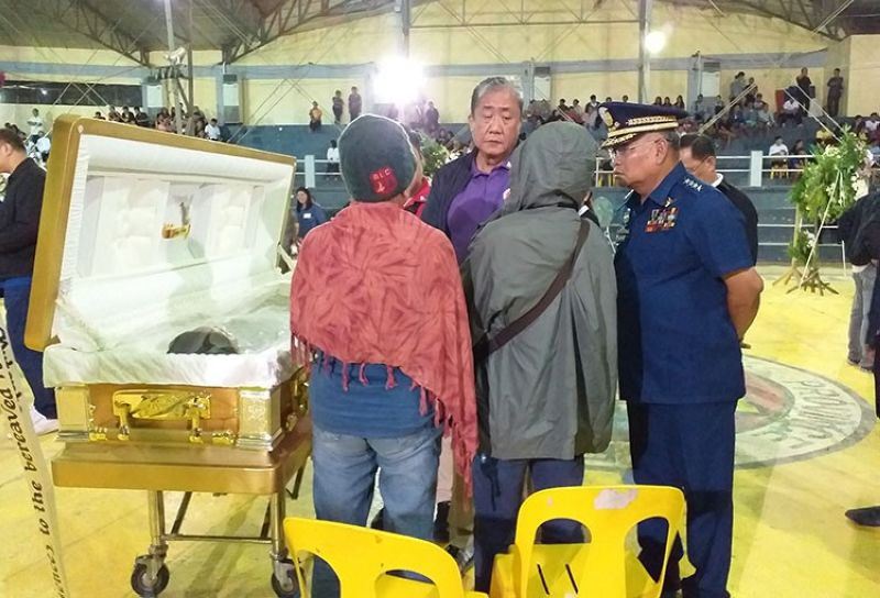 GUIMARAS. Department of Transportation Secretary Arthur Tugade talks to family members of some of the persons who died when three motorized bancas capsized in Iloilo-Guimaras Strait. The caskets bearing the bodies of some of the fatalities are placed at the Guimaras Provincial Multipurpose Gym. (Carolyn Jane Abello)