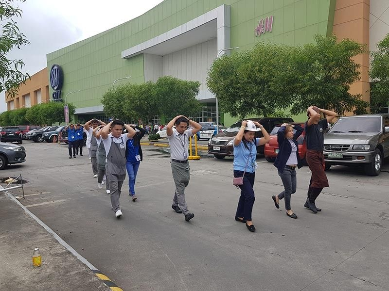 BACOLOD. Employees and mallgoers exit SM City Bacolod and are directed to the mall's command center during a simulation for the national earthquake drill, the third one held nationwide this year.