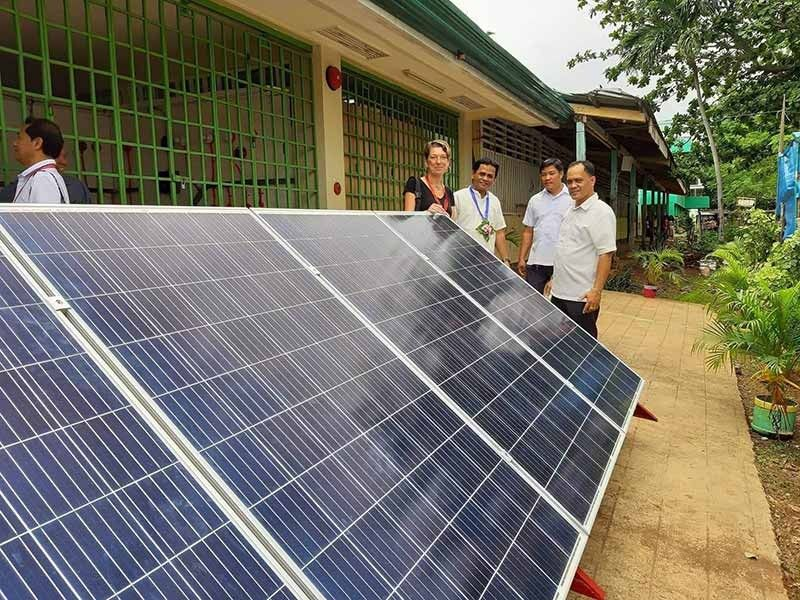 POWERING SCHOOLS. Sabine Schacknat (left), project director of Project Renewable Energy for Livelihood and Youth, inspects the solar panel array that serves as a teaching tool for the Electrical Installation and Maintenance tech-voc track offering at Daanbantayan National High School. (Contributed photo)