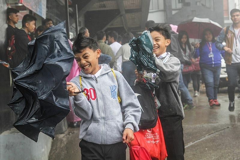 BAGUIO. High school students in both private and public schools struggle to keep dry as they head home early on a Friday, August 9, 2019 after the city government issued the suspension of classes for high school students at 12 noon due to inclement weather. (Photo by Jean Nicole Cortes)