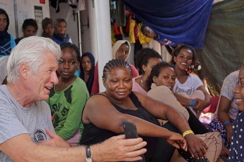 MEDITERRANEAN. Actor Richard Gere, left, talks with migrants aboard the Open Arms Spanish humanitarian boat as it cruises in the Mediterranean Sea, Friday, Aug. 9, 2019. Open Arms has been carrying 121 migrants for a week in the central Mediterranean awaiting a safe port to dock, after it was denied entry by Italy and Malta. (AP)