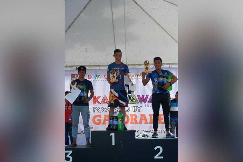 DAVAO. Kadayawan Run 2019 men's 25K champion former Davao City standout Sonny Wagdos, center, beams as he receives his prizes along with the next two finishers at the People's Park in Davao City Sunday, August 11, 2019. (Photo by Kenneth Ian Paradero)