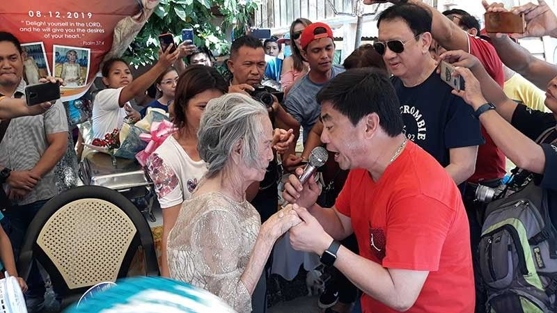 """CENTENNIAL SERENADE. Lapu-Lapu City Mayor Junard """"Ahong"""" Chan (carrying a microphone) tries to amuse Lucia Ycong Oyao by singing songs. Oyao, who turned 100 years old on Monday, Aug. 12, 2019, received P100,000 from the City Government. (SunStar photo/Alan Tangcawan)"""