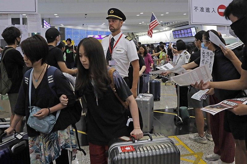 Passengers and flight crew arrive at Hong Kong International Airport, Monday, August 12, 2019. One of the world's busiest airports canceled all flights after thousands of Hong Kong pro-democracy protesters crowded into the main terminal Monday afternoon. (AP Photo)