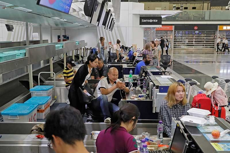 HONG KONG. Stranded travelers sit in the check-in counters at the Hong Kong International Airport, Monday, Aug. 12, 2019. One of the world's busiest airports canceled all flights after thousands of Hong Kong pro-democracy protesters crowded into the main terminal Monday afternoon. (AP Photo)