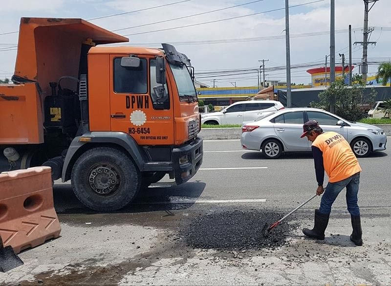 PAMPANGA. Workers of the DPWH-Pampanga 1st District Engineering Office Maintenance Section patch up potholes along JASA in Barangay Dolores, City of San Fernando. The potholes where caused by continuous monsoon rains. (Photo by Chris Navarro)