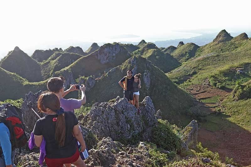 TOURISM BOOM. Tourists take a photo at the famous Osmeña Peak in Dalaguete, Cebu. Philippine Veterans Bank chairman and chief executive officer Roberto de Ocampo says tourism is one of the country's strengths to achieve high economic growth this year.  (SunStar file photo)