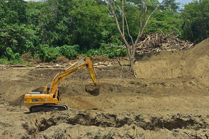 CLEARED. Heavy equipment continues to operate near Davao River in Barangay Ma-a, Davao City yesterday as personnel of the Department of Public Works and Highways work on the construction of the dike in the area. (Photo by Macky Lim)
