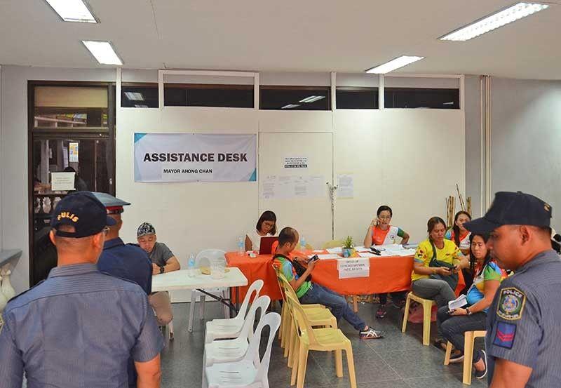STAYING PUT. Lapu-Lapu City Rep. Paz Radaza's staff set up an assistance desk outside their padlocked office. Beside them, Mayor Junard Chan's staff put up their own help desk. (SunStar photo/Alan Tangcawan)