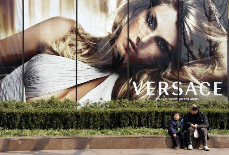 SHANGHAI, CHINA. In this February 15, 2008, file photo, a child and a man sit in front of the advertisement of Versace in Shanghai, China. Italian fashion house Versace has apologized in China for selling T-shirts that it said attached incorrect country names to cities, after a Chinese actress said the clothing was suspected of harming the country's territorial integrity and cut her ties with the company. Versace did not identify the T-shirt in a social media post Sunday, Aug. 11, 2019, but Chinese media said the item did not list Hong Kong and Macao as parts of China. Both former European colonies were returned to China in the late 1990s. (AP)
