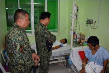 AWARD. Brigadier General Gilberto DC Cruz (center), Caraga Police Director, personally awards one of wounded policemen his medal while they are recovering from gunshot and shrapnel wounds at Caraga Regional Hospital in Surigao City. (Photo courtesy Caraga Region Police)