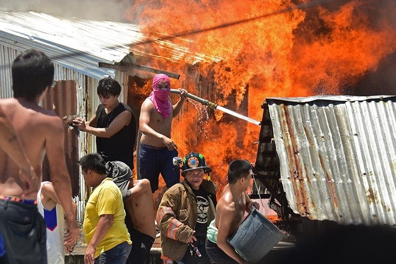 PULL OUT. Firefighters and residents pull away from the burning houses at Purok 3, Barangay 23-C Isla Verde in Davao City as the wind shifted toward their direction while pumping water on top of other houses Friday late morning. (Macky Lim)