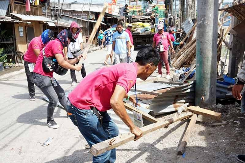 Opening sidewalks. A team from the Anti-Sidewalk Vending Task Force of Talisay City and local police demolish structures that obstructed the sidewalk beside the St. Joseph the Worker Parish in Sitio Sambagan, Barangay Tabunok. (SunStar File Photo / Alex Badayos)