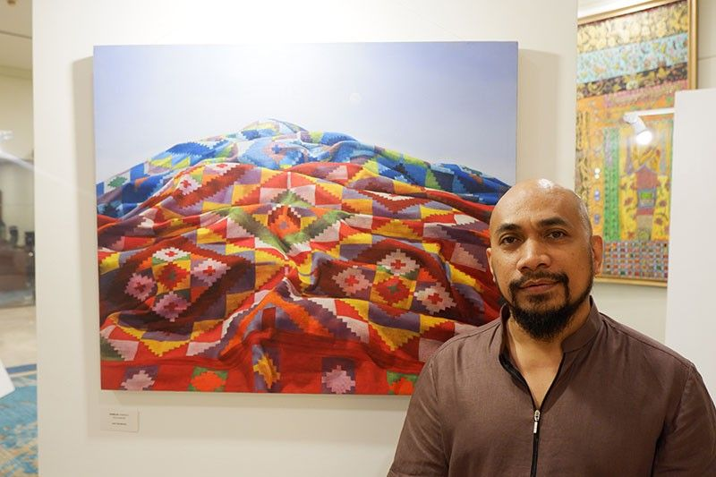 Joel Geolamen having a picture with his artwork, Kabilin. (Photo by Jinggoy Salvador)