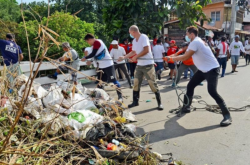 """CLEANUP. Retired basketball star and now Cebu City Councilor Donaldo """"Dondon"""" Hontiveros (right) helped  pull a sack of garbage from under the bridge on M. Velez St. while they cleaned the Guadalupe River on Saturday, Aug. 17, 2019. (SunStar photo / Alan Tangcawan)"""