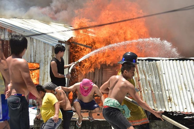 DAVAO. Residents of Isla Verde in Barangay 23-C trying to put out a fire razing some houses last Friday, August 16. (Photo by Macky Lim)