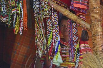 DAVAO. Nagpahulay samtang naghulat og mga bisita nga mamalit sa ilang produkto ang babayeng Matigsalog ilawom sa ilang tribal house sulod sa Kadayawan Village sa Magsaysay Park, Davao City. (Macky Lim)
