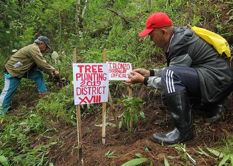 BAGUIO. Barangay officials tend to their plants at the Busol Watershed during a tree planting in Baguio City. A law is being proposed in the city that every family should plant and nurture a tree in their barangay. (Jean Nicole Cortes)