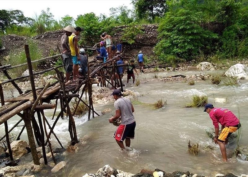 BAGUIO. Arub-uban, the Tinguian term for bayanihan, is practiced in Lagayan, Abra, as tribal folk handcraft a temporary wooden, hanging bridge that was severely damaged and swept away by raging currents. (Ezekiel Parado)