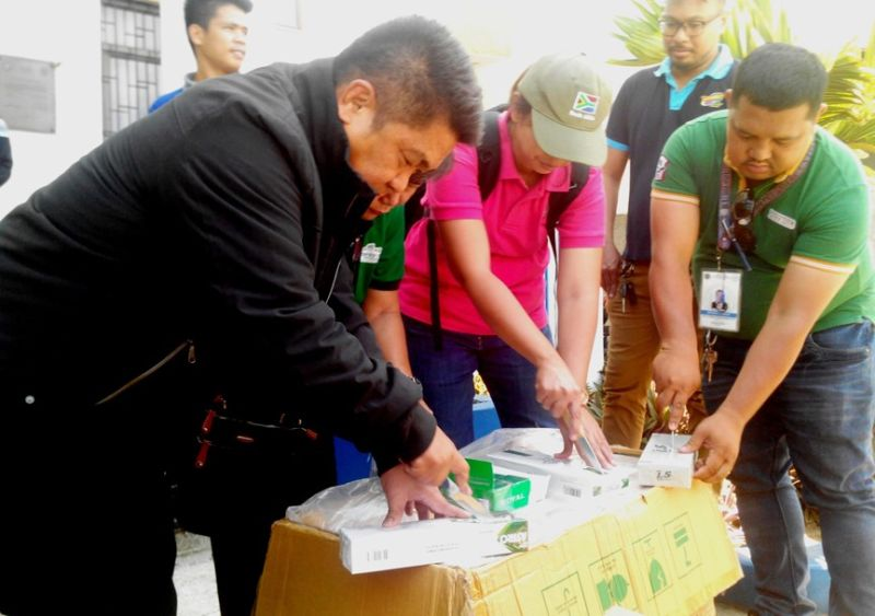 ZAMBOANGA. Segundo Sigmundfreud Barte Jr. (left), Bureau of Customs-Zamboanga District collector, leads Thursday, August 22, the destruction of P200,000 smuggled cigarettes at the port of Zamboanga. (Bong Garcia)
