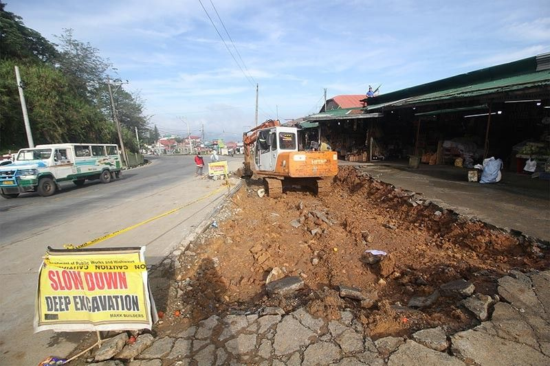 BAGUIO. A backhoe scours a portion of the Kadmangan trading center along Marcos Highway for road widening. (Jean Nicole Cortes)