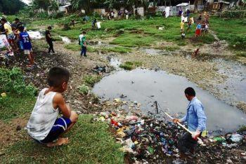 BASURA: Nagsud-ong ang usa ka bata samtang gikaykay sa usa ka volunteer ang nagtipun-og nga mga basura sa Mananga River atol sa clean up drive sa Biyernes sa buntag, Agusto 23. (Alex Badayos)