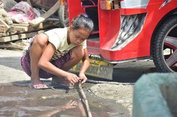DAVAO. Gibugkusan sa batang babaye og goma ang tubo sa tubig tungod sa kusog nga sirit gawas sa usa ka eskuwelahan sa Barangay 23-C Isla Verde, Davao City Biyernes, Agosot 23, 2019, aron likay sa dugang bayrunon sa tubig. (Macky Lim)