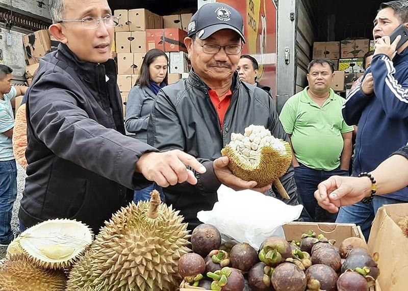 BAGUIO. Baguio City Mayor Benjamin Magalong samples some fruits from Mindanao together with Mindanao Development Authority (MinDA) Secretary Manny Piñol during the MinDA Fruit Festival on Session Road Sunday, August 25, 2019. (Photo by Aileen Refuerzo)