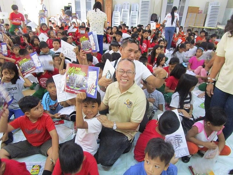 PAMPANGA. Alex Castro of Mabalacat Elementary School (MES) Batch 69 leads the distribution of Bale Matua coloring book to pupils at the school's Gabaldon Hall. He is joined by book illustrator Dodjie Aguinaldo, members of MES Batch 69, and school officials.