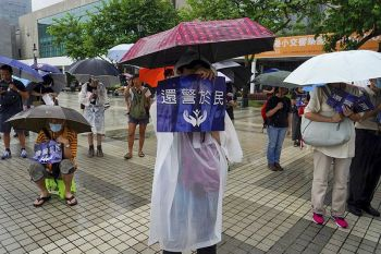 HONG KONG. People carrying umbrellas in the rain hold placards reading