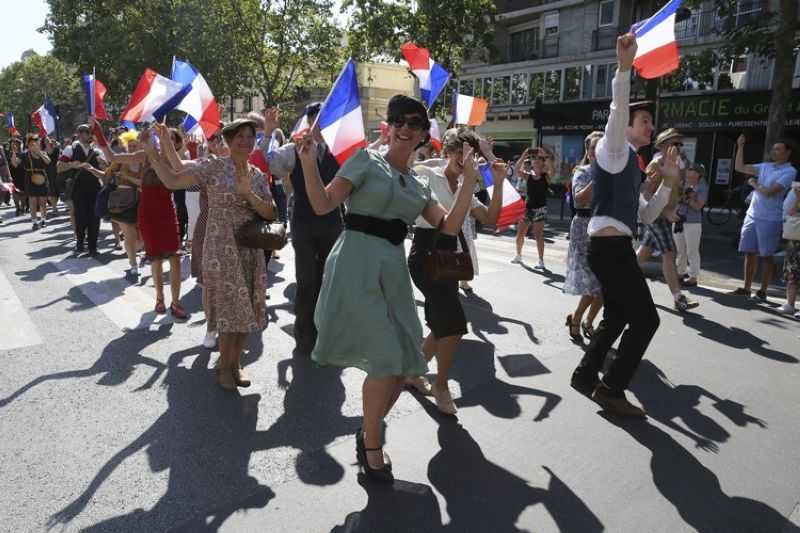 FRANCE. People dressed in World War II-era clothes dance in the street during celebrations of the liberation of Paris from Nazi occupation 75 years ago, in Paris, Sunday, August 25, 2019. Enthusiasts are retracing the entry of French and U.S. tanks into the city on Aug. 25, 1944. (AP)