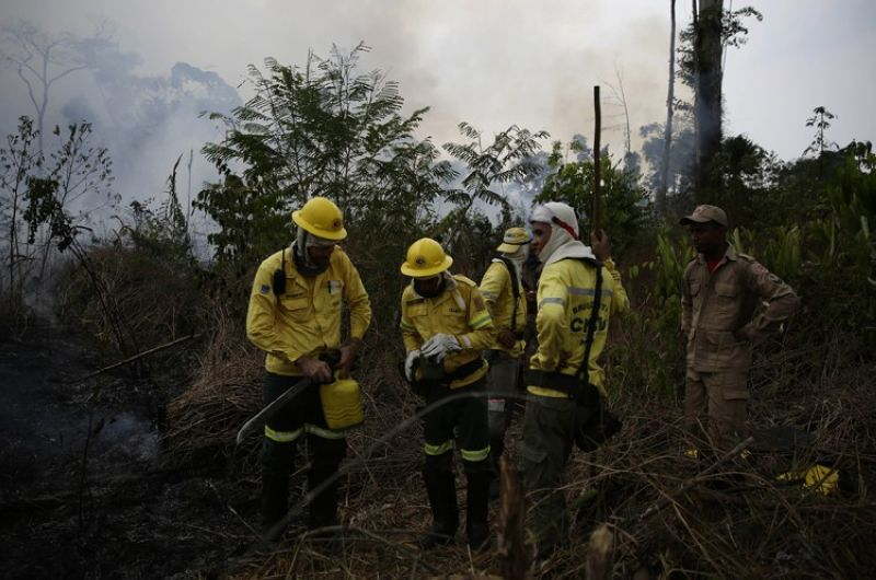 Firefighters rest briefly as they put out fires along the road to Jacunda National Forest, near the city of Porto Velho in the Vila Nova Samuel region which is part of Brazil's Amazon, Monday, August 26, 2019. The Group of Seven nations on Monday pledged tens of millions of dollars to help Amazon countries fight raging wildfires, even as Brazilian President Jair Bolsonaro accused rich countries of treating the region like a