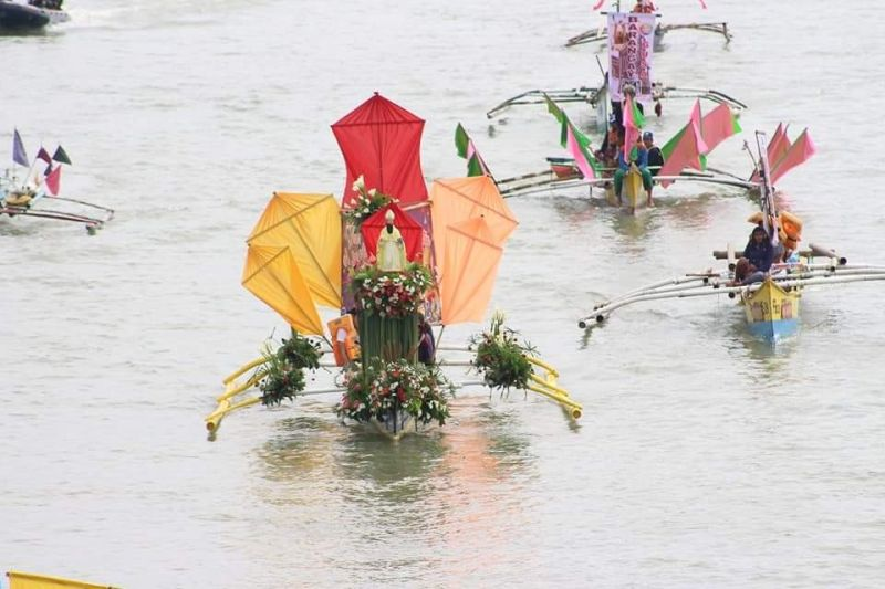 Religious statues depicting Catholic saints are adorned in flowers and colorful cloth as part of the fluvial procession in celebration of the Feast of St. Augustine in Cagayan de Oro City. The statues are boarded in boats traversing Cagayan river on Wednesday, August 28, 2019. (Roel Felicitas/City Information Office)