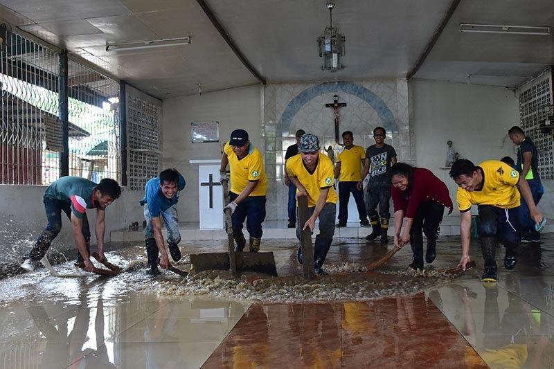 BAYANIHAN. Gitabangan sa mga residente ug personahe sa Emergency Response Team sa San Juan Village, Bangkal, Davao City kagahapon ang paglimpyo sa ilang kapilya human ang dakong baha nga nagbilin og mga lapok. MACKY LIM