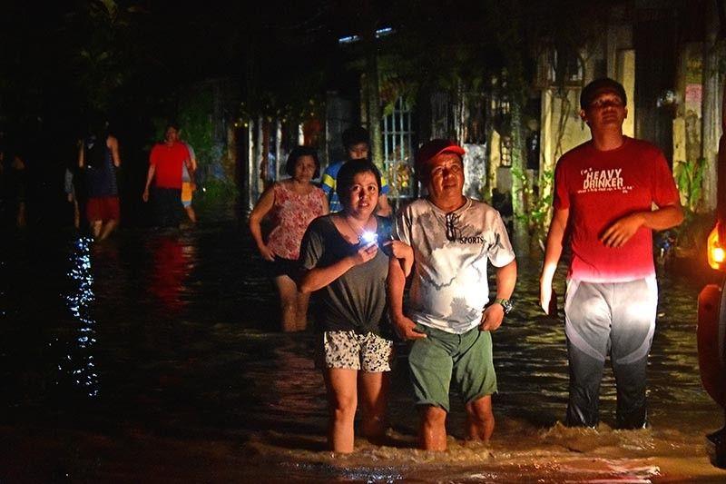 9264. Residents of NHA Bangkal in Davao City head back home around 1 a.m. Thursday despite the knee-deep floodwaters in some areas in Davao City due to the heavy rains in the mountains. Photo by Macky Lim