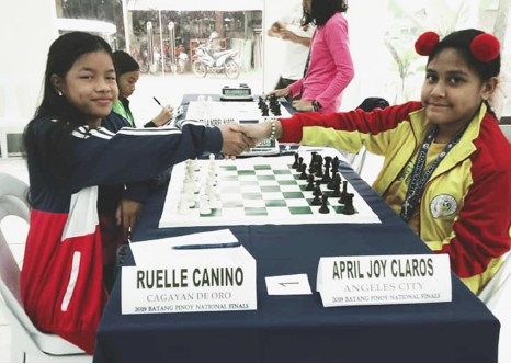 PALAWAN. Cagayan de Oro's Ruelle Canino (at left) shakes hands with April Joy Claros of Angeles City before the start of their fifth-round match in the Batang Pinoy standard chess event. (Supplied Photo)