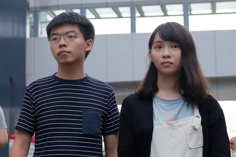 HONG KONG. In this June 18, 2019, photo, pro-democracy activists Agnes Chow, right, and Joshua Wong meet media outside government office in Hong Kong. Demosisto, a pro-democracy group in Hong Kong posted on its social media accounts that well-known activist Joshua Wong had been pushed into a private car around 7:30 a.m. Friday, August 30, 2019 and was taken to police headquarters. It later said another member, Agnes Chow, had been arrested as well. (AP)