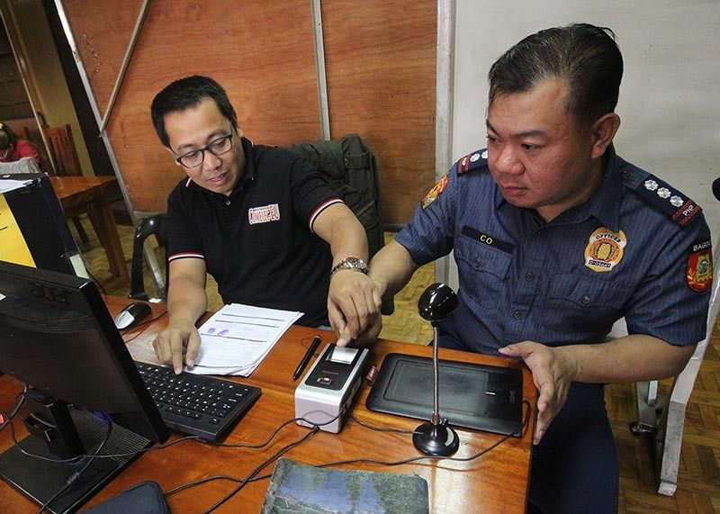 BAGUIO. Commission on Elections Baguio election officer John Paul Martinassists Baguio City Police Office (BCPO) director Police Colonel Allen Rae Co during the onsite voter's registration at the BCPO multipurpose hall on Friday, August 30. (Photo by Jean Nicole Cortes)