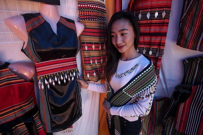 BAGUIO. Kristine Diki, the owner of a clothing brand in Kalinga showcase a modern dress accentuated with native weaving from Lubuagan Kalinga. Clothing products, bags, shoes, and other accessories accentuated with native weaving are sold at the Agri Trade fare during the celebration of the Bodong festival. (Photo by Jean Nicole Cortes)