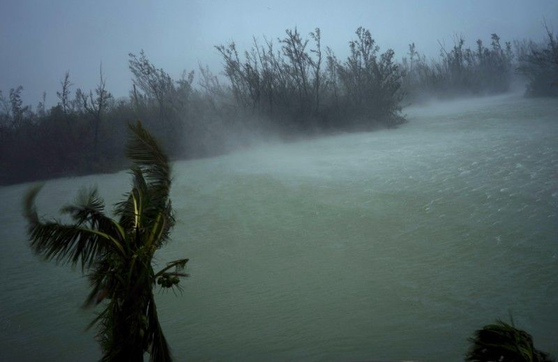 BAHAMAS. Strong winds from Hurricane Dorian blow the tops of trees and brush while whisking up water from the surface of a canal that leads to the sea, located behind the brush at top, seen from the balcony of a hotel in Freeport, Grand Bahama, Bahamas, Monday, September 2, 2019. Hurricane Dorian hovered over the Bahamas on Monday, pummeling the islands with a fearsome Category 4 assault that forced even rescue crews to take shelter until the onslaught passes. (AP)