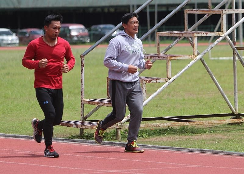 BAGUIO. Kevin Belingon and Eduard Folayang shares some light moment while having an early morning jog at the Baguio Athletic Bowl. (Photo by Roderick Osis)