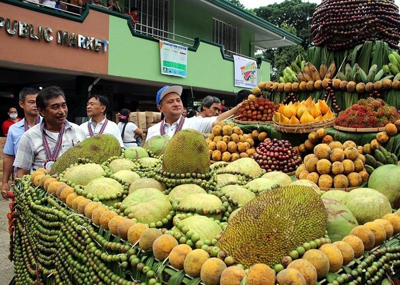 BENGUET. Benguet Governor Melchor Diclas and Sablan Mayor Manuel Munar Jr. sample locally grown fruits during the town's 5th fruit festival. (Lauren Alimondo)